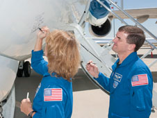 STS-135 mission specialists Sandy Magnus and Rex Walheim autograph a modified G-II Shuttle Training Aircraft recently acquired at Dryden. The astronauts visited Dryden Aug. 23, 2011.