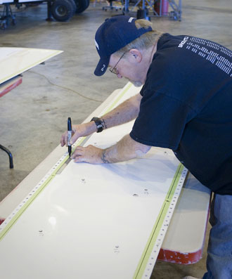Computer Sciences Corp. mechanic Jerry Roth marks holes for proper alignment of a blueprint on the wing skin of NASAs ER-2 No. 809. The aircraft is undergoing extensive maintenance.