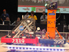 Robots from Antelope Valley High team 2339 and Lancaster High team 399 balance on the tilting bridge at the conclusion of a match at the San Diego FIRST regional competition