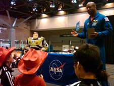 Former NASA astronaut and current NASA education chief Leland Melvin, flanked by a life-size model of the Buzz LIghtyear figure, enthralls a trio of youngsters at the FIRST Robotics Championships in St. Louis.