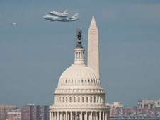 Shuttle Discovery flying by Washington Monument and the Capital Building in Washington D. C.