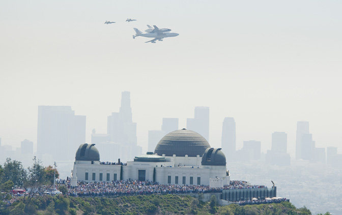 Thousands of spectators gathered at Griffith Observatory in Griffith Park to catch a glimpse of space shuttle Endeavour atop its 747 carrier aircraft as it flew between the observatory and downtown Los Angeles, visible through the haze in the background, during its low-level flyover of Los Angeles