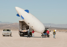 Cessna researchers prepare to launch a blimp that carries several microphones used to record sonic booms for the FaINT project. The tethered blimp flies at an altitude of about 3,000 feet above ground to collect sonic boom data at that altitude.
