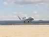 NASA Global Hawk No. 872 flares for landing at Edwards Air Force Base, Calif. The autonomously operated unmanned research aircraft will be flying at high altitude over the Pacific Ocean during the ATTREX environmental science mission.