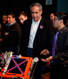 Gabe Ruiz of the Lancaster (Calif.) High School Eagle Robotics team details features of the shooter mechanism on the team's ENIAC robot entry in the 2013 FIRST Robotics Competition to NASA Dryden Flight Research Center director David McBride.