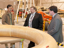 Tony Chen, left, discusses the mechanical testing of the Flight Loads Laboratory's upcoming Hypersonic Inflatable Aerodynamic Decelerator to Peck and Adams.