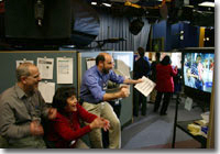 JPL staff members respond excitedly as live images from the JPL control room relate the landing progress of the Rover Opportunity