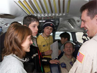Photo: NASA DC-8 pilots Craig Bomben, standing in foreground, and Bill Brockett, seated, explain the DC-8 to Chilean students onboard the aircraft in Punta Arenas, Chile.