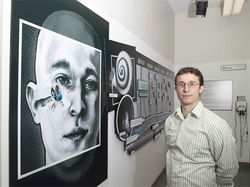 Image of Nick Hawes as he stands beside a mural he created.