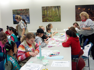 Girl Scouts participate in rocket-making activity with NASA advisor.