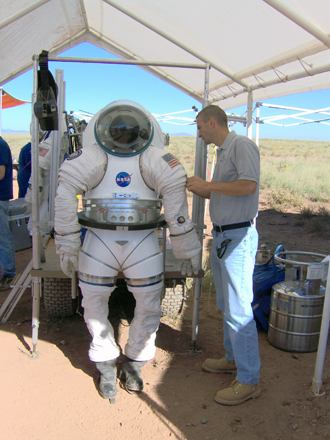 NASA employee makes adjustments to spacesuit during testing in a desert setting.