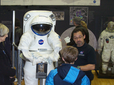 A traveling space suit exhibit is shown at a local venue.