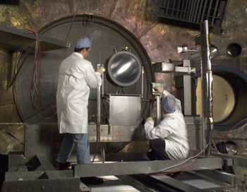 Image of 2 men testing NASA's Evolutionary Xenon Thruster (NEXT) in the Electric Propulsion Laboratory.