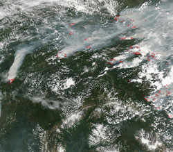 This image from the Moderate Resolution Imaging Spectroradiometer on NASA's Aqua satellite shows forest fires and thick smoke over Alaska and Canada on July 13, 2004.