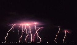 Photograph of a nighttime thunderstorm near Norman, Oklahoma, containing several cloud to ground lightning strikes.