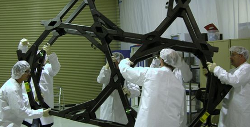 Scientists and Engineers at Northrop Grumman working with the Backplane or 'Spine' of the JWST.