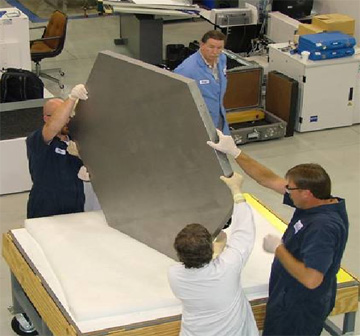 Engineers at Axsys Technologies work with one of the mirrors of the JWST.