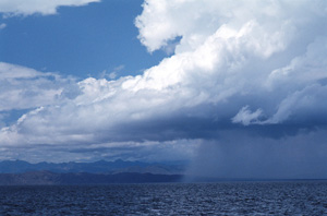 Photo of heavy rainfall pouring over the Pacific Ocean.