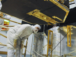 Astronaut John Grunsfeld checks clearances on the bottom of the Fine Guidance Sensor as it is being installed into the Hubble Mockup inside the Goddard cleanroom. This sensor is also slated to be installed during Servicing Mission 4.