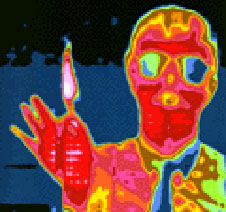 This infrared image shows a man holding up a lighted match