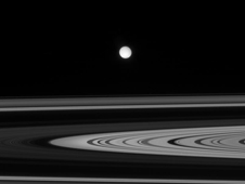 Enceladus is seen here as a white disk across the unilluminated side of the rings of Saturn
