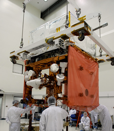 General Dynamics technicians watch as GLAST is moved toward a work stand.