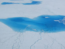 Scientists survey surface lakes brought about by seasonal melt of the Greenland Ice Sheet in July 2006.