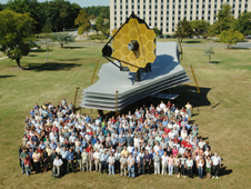 A large crowd of people stand outside in front of a full-scale model of the James Webb Space Telescope.