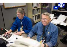 HST engineers Steve Leete, left, and Ron Sheffield of take a short break from making entries in the flight log while on console in the Flight Control Room at Johnson Space Center during Servicing Mission 4 to Hubble.