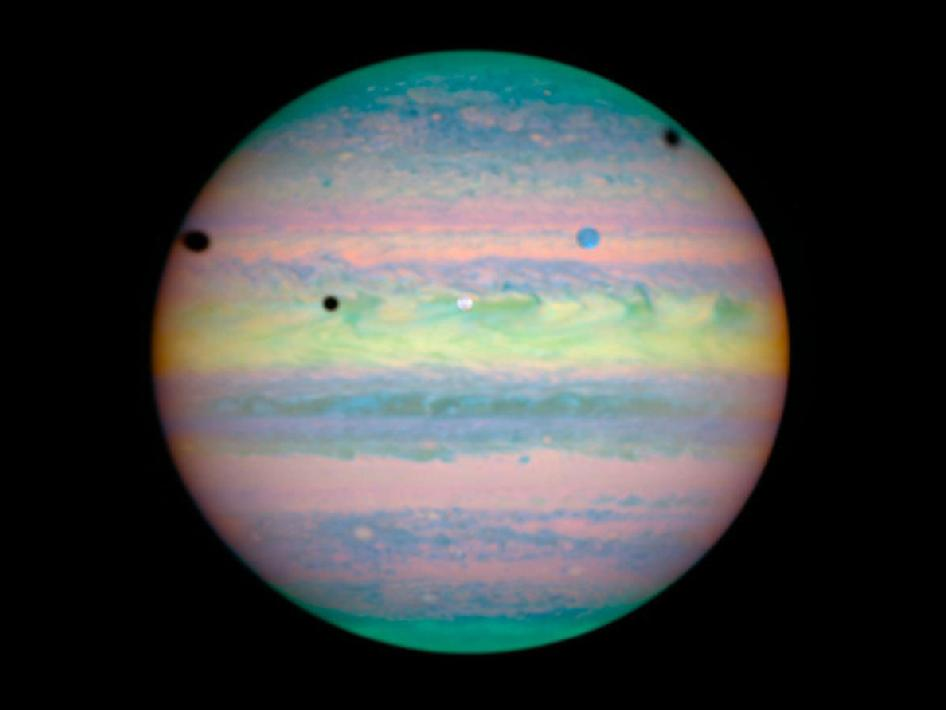 Jupiter, in pastel colors because the observation was taken in near-infrared light, experiences a rare alignment of three of its large moons; Io, Ganymede, and Callisto.
