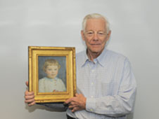Bob holding a portrait drawn of him when he was five years old.