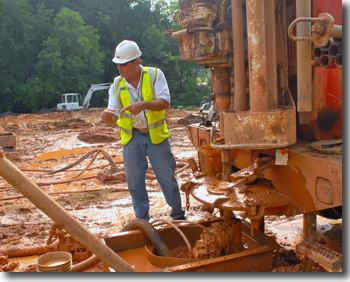 John is shown here doing field work, coordinating a construction project involving 100 geothermal wells that are being dug at NASA's Goddard Space Flight Center.