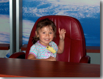 John's granddaughter Isabella Gauthier poses for the camera during their tour of the TV Studio at NASA's Goddard Space Flight Center.