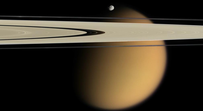 Titan just beyond Saturn's rings.