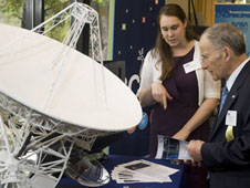 two people interact near a model of a satellite dish