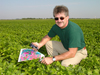 farmer kneels in field with map and cell phone