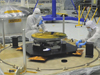 technicians inspect the Webb telescope's secondary mirror in a clean room at NASA Goddard