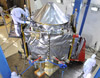 Shiny spacecraft tended to by technicians in paper suits in a cleanroom