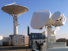 Large and small radar arrays sprout like mushrooms from a field and shipping containers against a blue sky