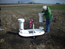 guy in a green coat installs a collection pipe on a rain gauge in a stubble field