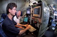 Image of two scientists examining data onboard an airplane.