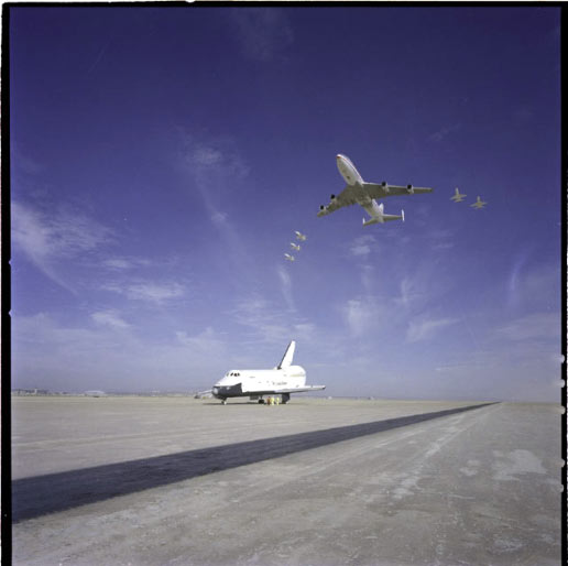 The NASA 747 carrier aircraft and five T-38 aircraft fly over the Space Shuttle Orbiter 101