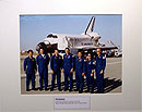 Astronauts pose for a picture in front of space shuttle Discovery