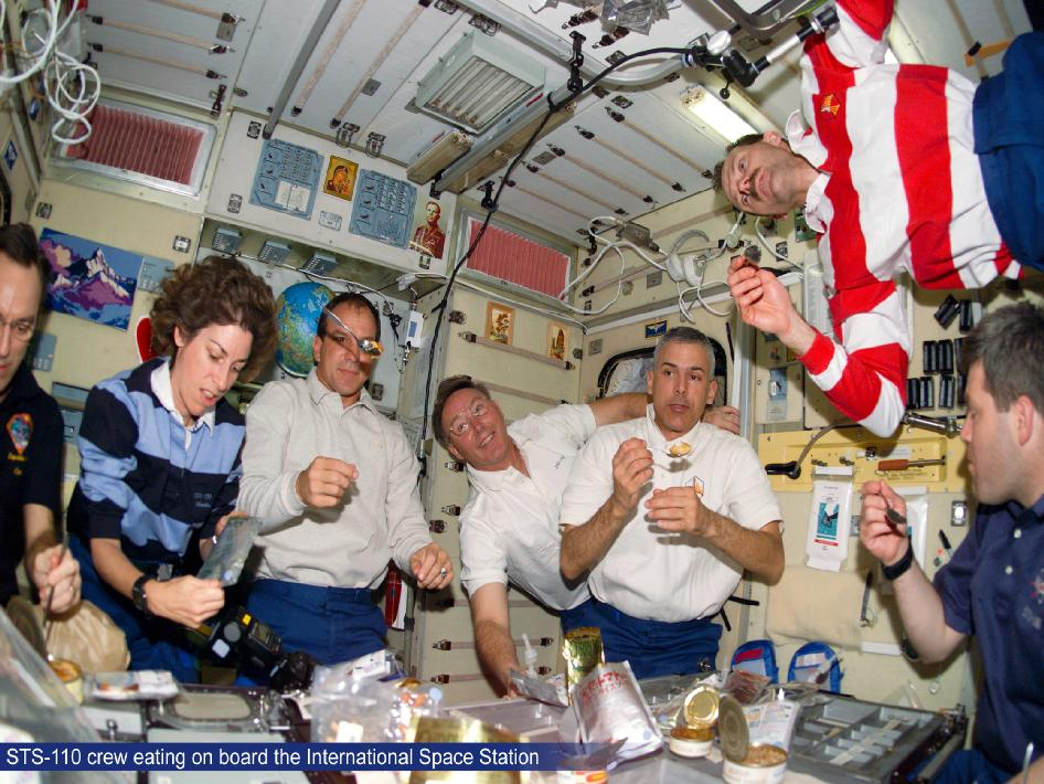 STS-110 crew eating on board the ISS