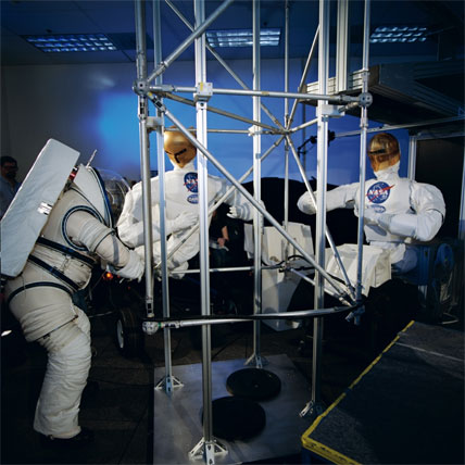 Two Robonauts work hand-in-hand with astronaut Nancy J. Currie during an evaluation at the Dexterous Robotics Laboratory to determine the capabilities of human beings and robots to perform certain extravehicular tasks.