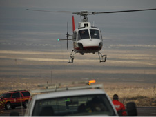 An emergency airlift helicopter begins descent to rescue crash victim