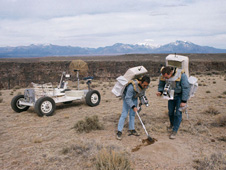 S71-23772  --- Apollo 15 astronauts practice collecting samples during a traverse in the Taos, New Mexico, area.  The Grover sits behind the astronauts