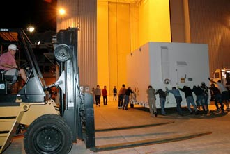Workers roll one of two containers with the Mars Reconnaissance Orbiter equipment into the Payload Hazardous Servicing Facility, Kennedy Space Center