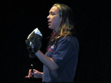Engineer Heather Paul holds astronaut accessories for students to see.