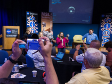 Participants in a NASA Social to preview the landing of the Mars Science Laboratory's (MSL) Curiosity rover photograph NASA and JPL personnel